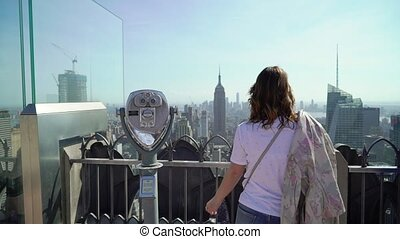 Young woman using scope at observation deck viewpoint
