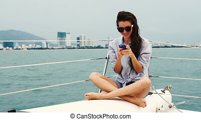 Young woman using smartphone and smiling while sitting on a yacht