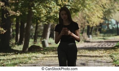 Young woman using smartphone and walking in park in city