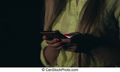 Young woman using smartphone at night