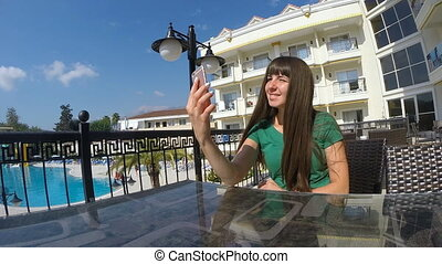 Young woman using smartphone for video call from hotel. Girl sends greetings to his relatives or friends. Close up Slow motion
