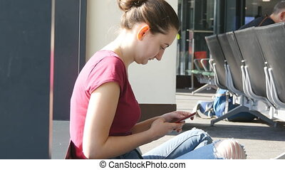 Young woman using smartphone in airport waiting lounge. Girl with smart phone at terminal during expectations of flight. Close up