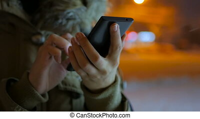 Young woman using smartphone in the city at night