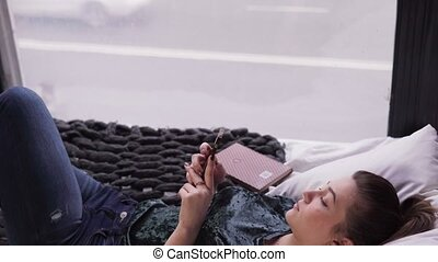 Young woman using smartphone on bed by window overlooking city street