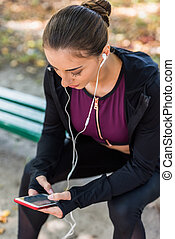 woman using smartphone on bench in park