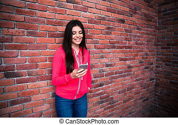 Young woman using smartphone over brick wall