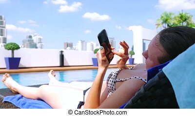 Young woman using smartphone sends sms on sunbed by pool on urban architecture background. 3840x2160