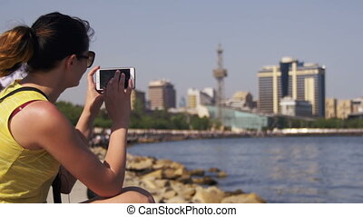 Young Woman using Smartphone Sitting on Embankment near the Sea and Skyscrapers of Megapolis