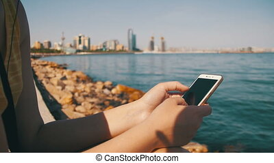 Young Woman using Smartphone Sitting on Embankment near the...