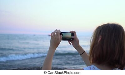 Young woman using smartphone to take a photo on the beach