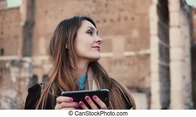 Young woman using smartphone while exploring the Roman Forum. Girl walking in city, spending vacation in Rome, Italy.