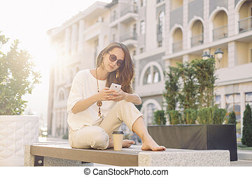 Young woman using smartphone while resting on wooden bench.