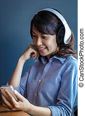 Young woman using smartphone with wireless headphone - Young...