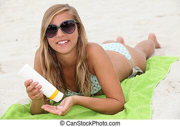 Young woman using sun cream on the beach