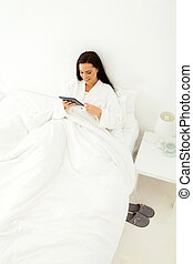 young woman using table computer in bed