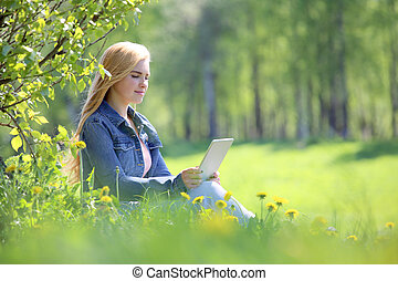 Young woman using tablet in park