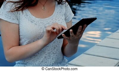 Young woman using tablet in the street closeup footage