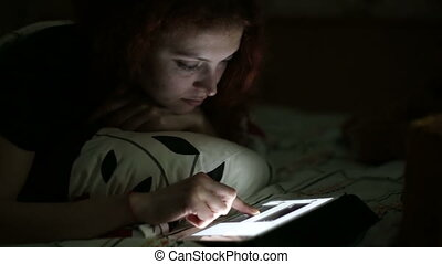 Young woman using tablet lying on bed at home at night