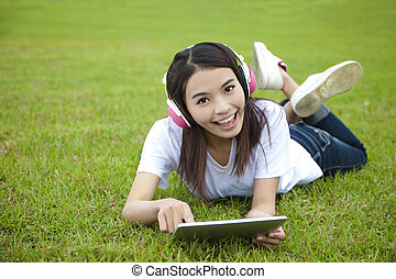 young woman using tablet pc on the grass