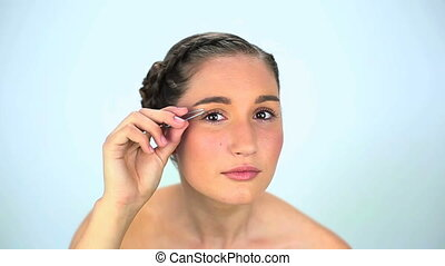 Young woman using tweezers on white background