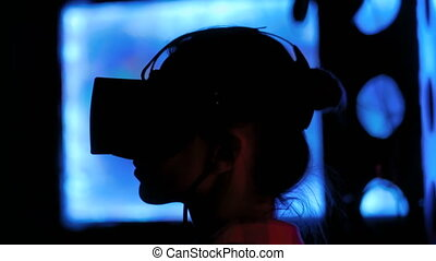 Young woman using virtual reality headset at dark interactive exhibition