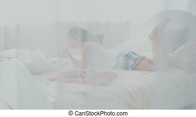 Young woman using wireless technology lying on a white bed at home. Girl chatting on laptop during breakfast.
