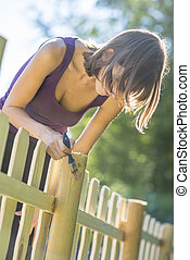 Young woman varnishing a wooden fence
