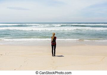 Young woman, view from the back, standing on shore watching the ocean.