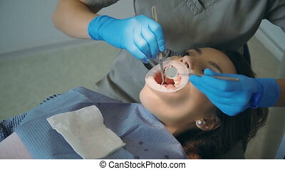 Young woman visiting the dental office. Female lying in...