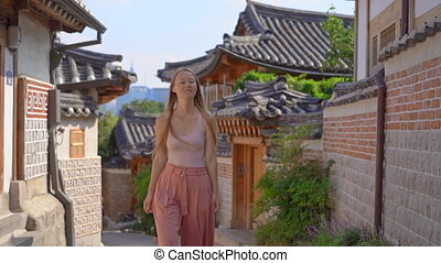 Young woman visits the busy touristic historical street ...