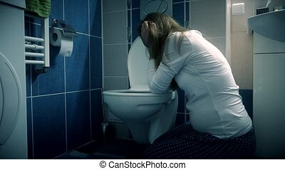 Young woman vomiting in bathroom wc - morning sickness...