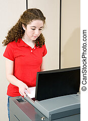 Young Woman Voting - Young woman voting on new optical scan...