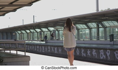 young woman waiting for a train at platform at the station portugal