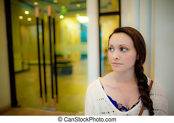 Young woman waiting in front of hotel door in Asia