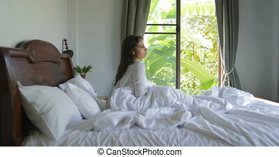 Young Woman Waking Up In Bed Coming To Window Stretching Arms, Beautiful Girl In Bedroom Morning