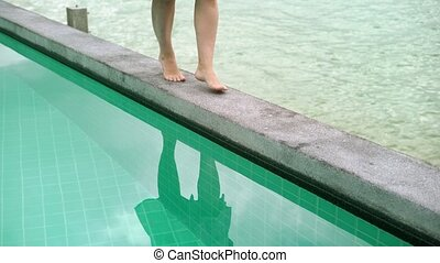 Young woman walk by the pool