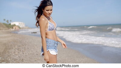 Young woman walking across a tropical beach