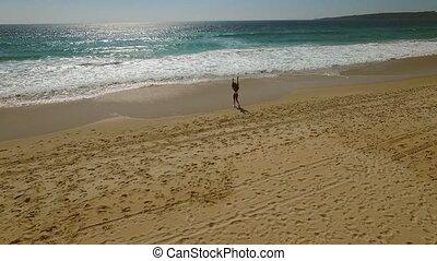 Young woman walking alone along a beach