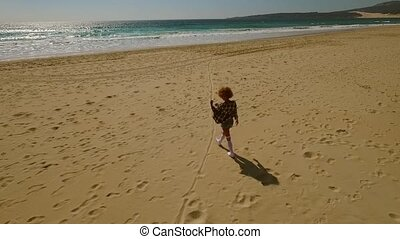 Young woman walking alone along a beach