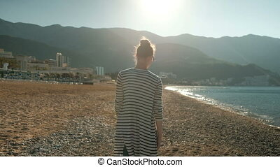 Young woman walking along beach on warm day.