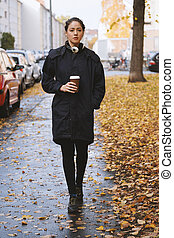 young woman walking along city street in autumn