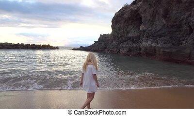 woman walking along the beach - young woman walking along...