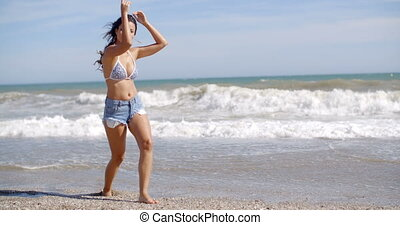 Young woman walking along the surf