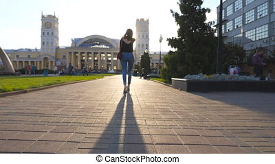 Young woman walking along urban street in morning....