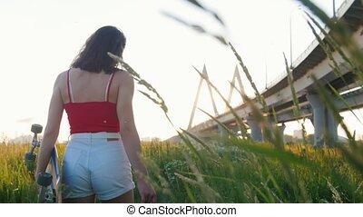 Young woman walking among high grass holding a skateboard - sunset - urban bridge