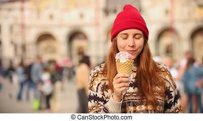 Young woman walking at the city square and eat the icecream - Mid shot