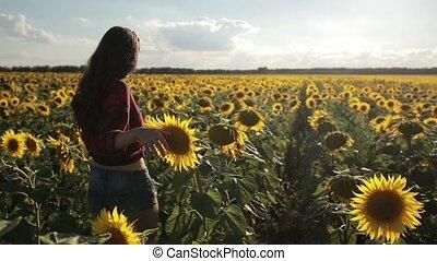 Young woman walking away in sunflower field