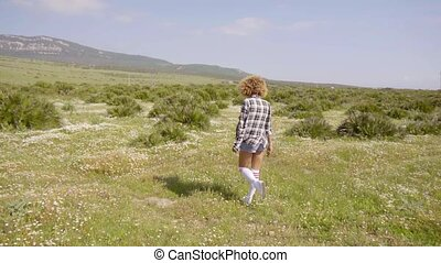 Young woman walking away through open countryside with low...