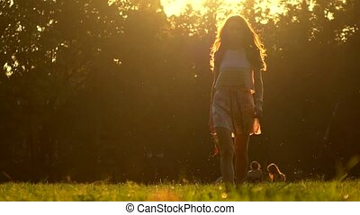 Young woman walking barefoot on the grass holding her high heel shoes in hand, 4K zoom out shot. Warm summer sunset colors