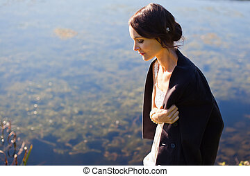 Young woman walking by water in sunlight